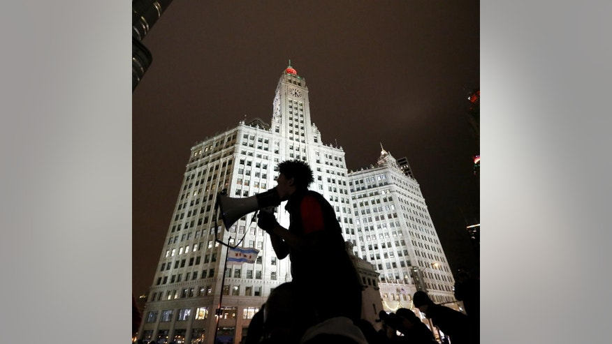 A protester is silhouetted against Chicago's famed Wrigley Building as he directs others to shutdown traffic on both sides of the Michigan Ave. bridge over the Chicago River, Wednesday, Nov. 25, 2015, one day after murder charges were brought against police officer Jason Van Dyke in the killing of 17-year-old Laquan McDonald. (AP Photo/Charles Rex Arbogast)