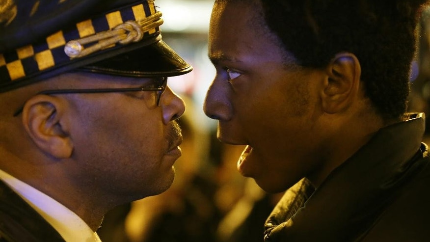 "Lamon Reccord, right, stares and yells at a Chicago police officer ""Shoot me 16 times"" as he and others march through Chicago's Loop Wednesday, Nov. 25, 2015, one day after murder charges were brought against police officer Jason Van Dyke in the killing of 17-year-old Laquan McDonald. (AP Photo/Charles Rex Arbogast)"