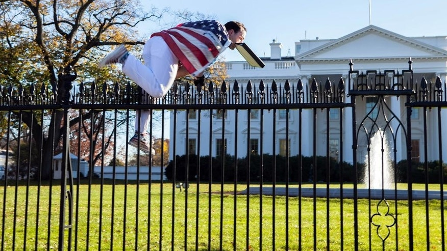 In this photo provided by Vanessa Pena, a man jumps a fence at the White House on Thursday, Nov. 26, 2015, in Washington. The man was immediately apprehended and taken into custody pending criminal charges, the Secret Service said. President Barack Obama and his wife and daughters were spending Thanksgiving the holiday at the White House. (Vanessa Pena via AP) MANDATORY CREDIT