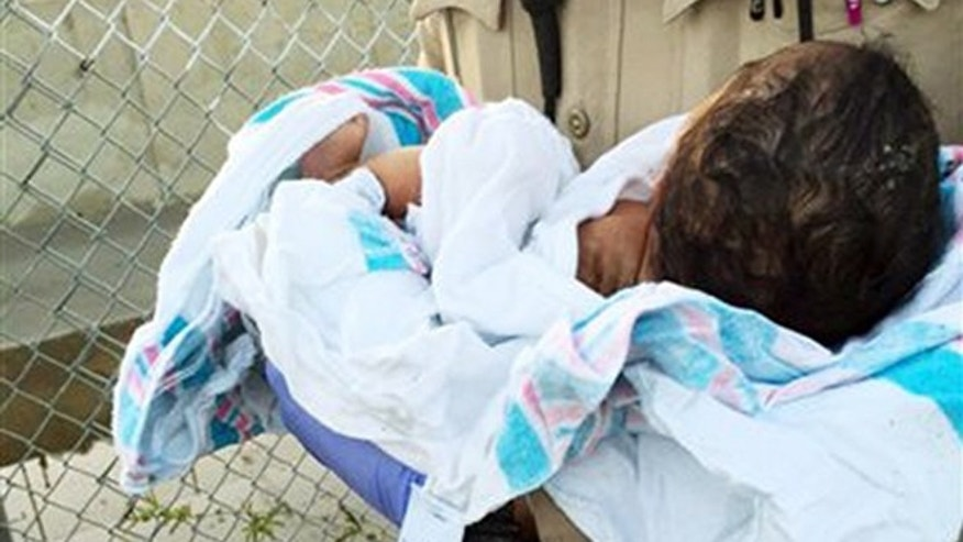 This Friday, Nov. 27, 2015 photo provided by the Los Angeles County Sheriff's Department shows an unidentified deputy holding an infant girl where she was found abandoned under asphalt and rubble, lower left, near a bike path in Compton, Calif., as they seek the public's help in identifying her.  (Los Angeles County Sheriff's Department via AP)