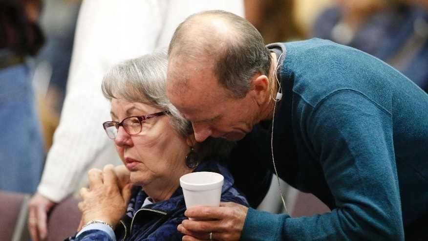 Scott Dontanville, front, co-pastor of the Hope Chapel, consoles a congregant before service early Sunday, Nov. 29, 2015, in northeast Colorado Springs, Colo. University of Colorado-Colorado Springs police officer Garrett Swasey, who was one of the three victims of a shooting at a nearby Planned Parenthood clinic Friday, was a member of the congregation. (AP Photo/David Zalubowski)