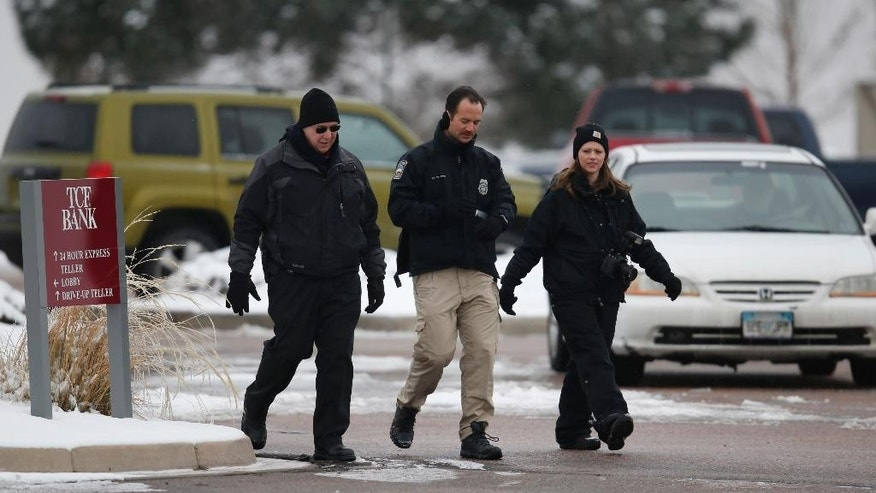 Crime scene investigators search for evidence in a strip mall parking lot near a Planned Parenthood clinic Sunday, Nov. 29, 2015, in northwest Colorado Springs, Colo. (AP Photo/David Zalubowski)