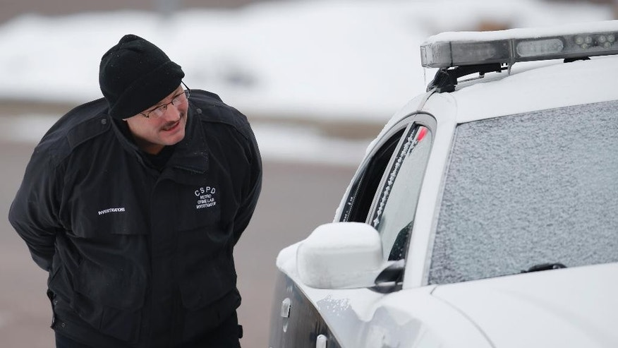 A crime scene investigator looks over one of the police vehicles damaged during Friday's shooting near a Planned Parenthood clinic Sunday, Nov. 29, 2015, in northwest Colorado Springs, Colo. Three people were killed in Friday's five-hour standoff, including a police officer, while clinic staffers and patients hid on site. Suspect Robert Lewis Dear is expected to make his first court appearance Monday.  (AP Photo/David Zalubowski)