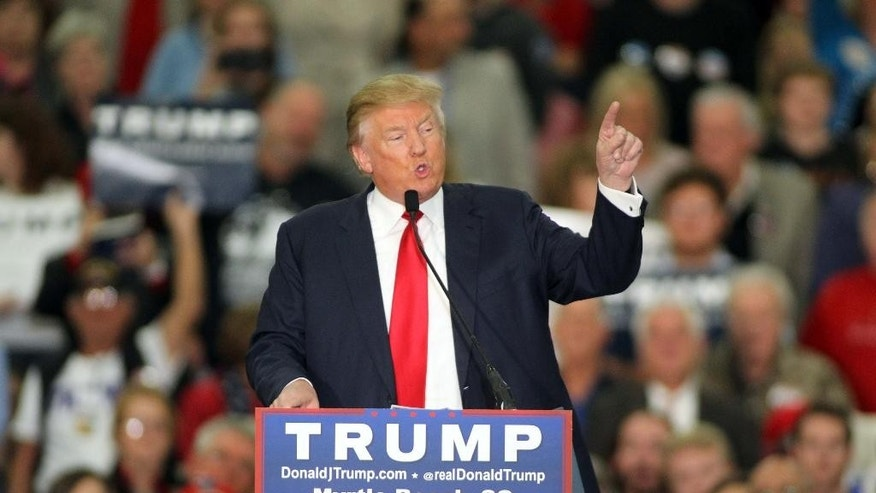 "FILE - In this file photo taken on Nov. 24, 2015, Republican presidential candidate Donald Trump speaks during a campaign event at the Myrtle Beach Convention Center in Myrtle Beach, S.C. Some leading Republican presidential candidates seem to view Muslims as fair game for increasingly harsh words they might not dare use against any other group for fear of the political cost. So far, that strategy is winning support from conservatives influential in picking the nominee.  Since the attacks that killed 130 people in Paris, GOP front-runner Trump has said he wants to register all Muslims in the U.S. and surveil American mosques. He has repeated unsubstantiated claims that Muslim-Americans in New Jersey celebrated by the ""thousands"" when the World Trade Center was destroyed on Sept. 11, 2001. (AP Photo/Willis Glassgow, File)"