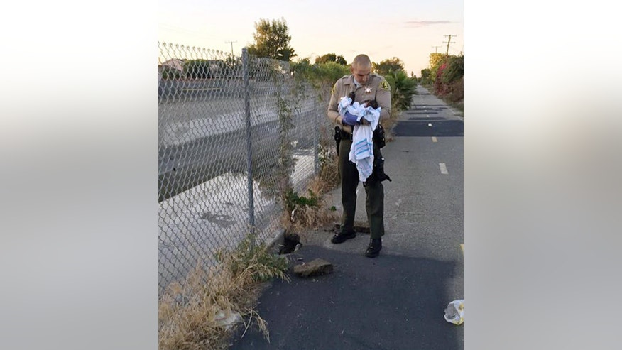 This Friday, Nov. 27, 2015 photo, provided by the Los Angeles County Sheriff's Department shows an unidentified deputy holding an infant girl where she was found abandoned under asphalt and rubble, left, near a bike path in Compton, Calif., as they seek the public's help in identifying her. The baby girl, who was wrapped in a blanket, was believed to be only less than a week old when two deputies found her Friday afternoon. She was taken to a hospital, where she is listed in stable condition. (Los Angeles County Sheriff's Department via AP)