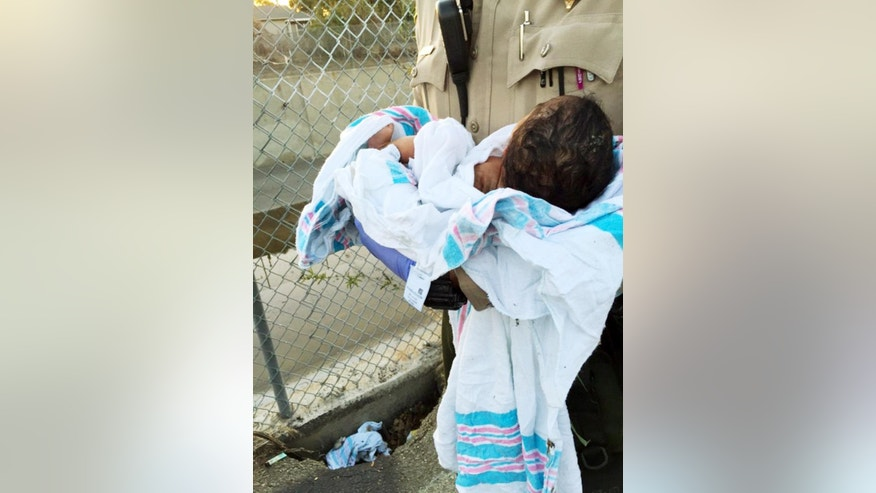 This Friday, Nov. 27, 2015 photo provided by the Los Angeles County Sheriff's Department shows an unidentified deputy holding an infant girl where she was found abandoned under asphalt and rubble, lower left, near a bike path in Compton, Calif., as they seek the public's help in identifying her. The baby girl, who was wrapped in a blanket, was believed to less than a week old when two deputies found her Friday afternoon. She was taken to a hospital, where she is listed in stable condition. (Los Angeles County Sheriff's Department via AP)