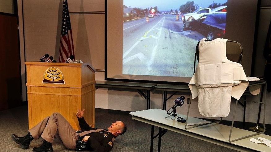 Col. Daniel Fuhr of the Utah Highway Patrol demonstrates, during a press conference in Taylorsville, Monday, Nov. 30, 2015, what happened during an officer involved shooting in Layton, on August 28, 2015. At right is the protective vest Lt. Paul Kotter was wearing during the incident. Kotter survived despite being shot three times during a shootout after a traffic stop near Hill Air Force Base and is returning to work three months after the incident.  (Ravell Call/The Deseret News via AP)  SALT LAKE TRIBUNE OUT; MAGS OUT; MANDATORY CREDIT; TV OUT