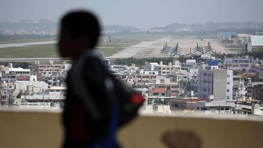 A child looks at the U.S. Marine Corps Futenma Air Station and the surrounding area from an observation deck at a park in Ginowan, Okinawa Prefecture on southern Japan in March 2015.  (AP Photo/Eugene Hoshiko)