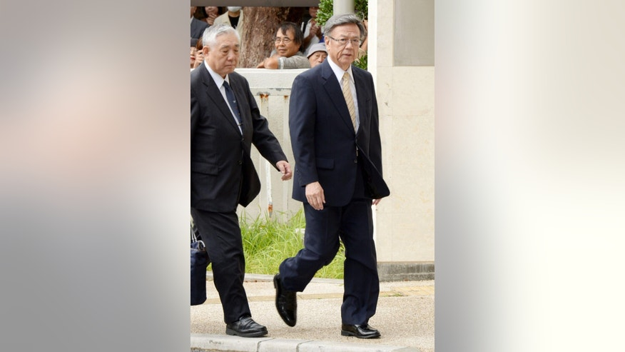 Okinawa Gov. Takeshi Onaga, right, arrives at a court for a hearing in Naha, Wednesday, Dec. 2, 2015. Hearings began Wednesday in a legal battle between the Japanese government and local officials in Okinawa over plans to move a U.S. military air base on the southern island.  (Kyodo News via AP) JAPAN OUT, MANDATORY CREDIT