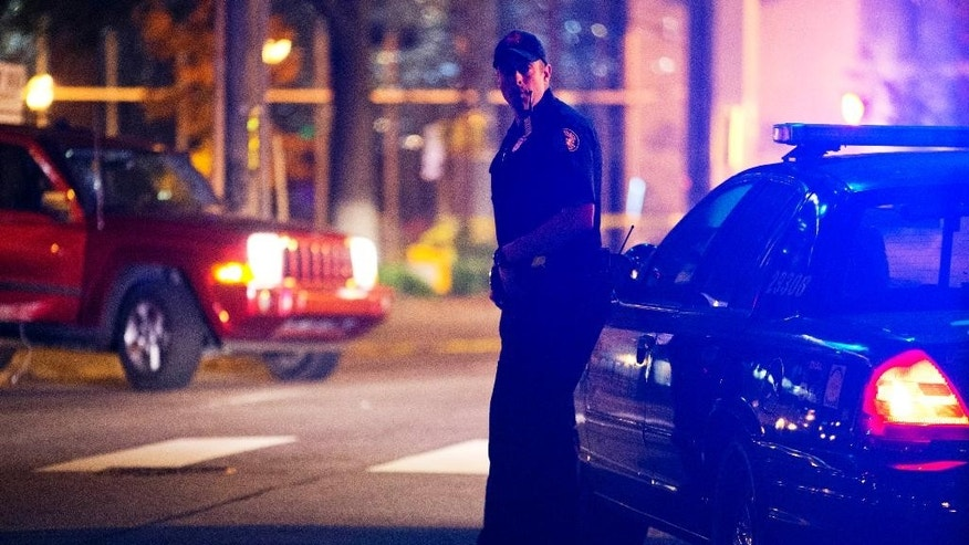 A police officer stands near the scene of an officer-involved shooting, Tuesday, Dec. 1, 2015, in downtown Atlanta, that left one person dead after an officer attempted to stop a vehicle on Monday. (AP Photo/David Goldman)