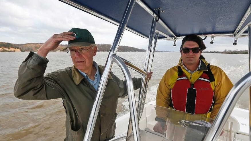 In this Tuesday, Nov. 17, 2015 photo, Hill Wellford, left, and Richard Moncure, of the Friends of the Rappahannock, ride along Fones Cliff in a boat on the Rappahannock river in Richmond County, Va. The two are against a luxury development of hundreds of homes and other attractions on a cliff overlooking a critical feeding area for migratory waterfowl. (AP Photo/Steve Helber)