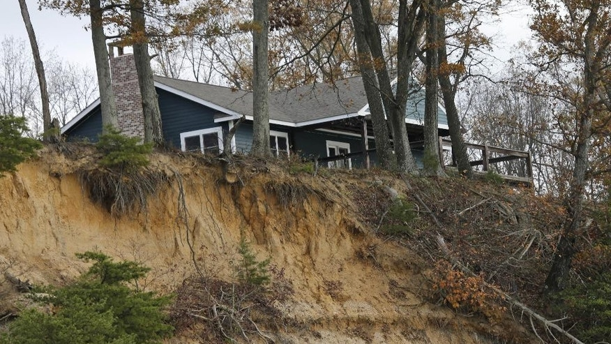 In this Tuesday, Nov. 17, 2015 photo, eroding shoreline is seen near a home at Fones Cliff on the shores of the Rappahannock river in Richmond County, Va. A developer is proposing a luxury development of hundreds of homes and other attractions on a cliff overlooking this critical feeding area for migratory waterfowl. (AP Photo/Steve Helber)