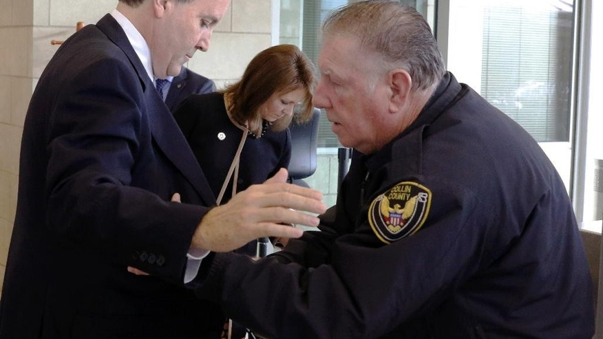 Texas Attorney General Ken Paxton and his wife Angela go through security before entering the Collin County Courthouse for a hearing on Tuesday, Dec.1, 2015 in McKinney, Texas.  Paxton is accused of encouraging wealthy investors to pump more than $100,000 into a tech startup called Servergy without revealing he was being paid by the company.  (David Woo/The Dallas Morning News via AP, Pool)