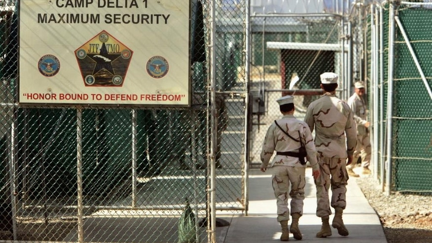 FILE - In this June 27, 2006 file photo, reviewed by a U.S. Department of Defense official, U.S. military guards walk within Camp Delta military-run prison, at the Guantanamo Bay U.S. Naval Base, Cuba. A federal appeals court will reconsider the legality of the only remaining conviction of a Guantanamo Bay detainee who once served as Osama bin Laden's personal assistant. The full U.S. Court of Appeals for the District of Columbia Circuit heard arguments Tuesday after a divided three-judge appeals panel earlier ruled that the conspiracy case against Ali Hamza al-Bahlul is legally flawed because conspiracy is not a war crime.  (AP Photo/Brennan Linsley, File)