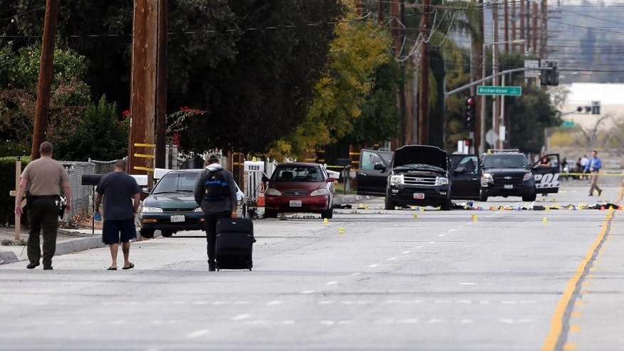 Residents are escorted to their home near a Black SUV that was involved in Wednesday's police shootout with suspects, Thursday, Dec. 3, 2015, in San Bernardino, Calif. A heavily armed man and woman dressed for battle opened fire on a holiday banquet for his co-workers Wednesday, killing multiple people and seriously wounding others in a precision assault, authorities said. Hours later, they died in a shootout with police. (AP Photo/Chris Carlson)