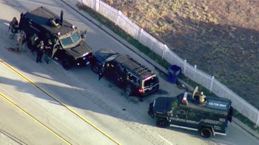 In this image taken from video, armored vehicles surround an SUV following a shootout in San Bernardino, Calif., Wednesday, Dec. 2, 2015. The scene followed a military-style attack that killed multiple people and wounded others at a California center that serves people with developmental disabilities, authorities said.   (KTTV via AP)