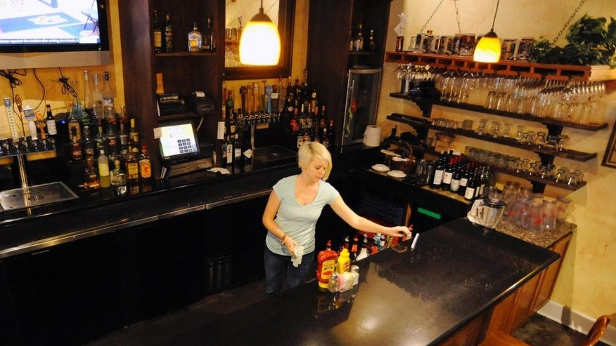 This photo taken Tuesday, Nov. 17, 2015, shows bartender Anna Gissendanner inside Marble City Grill in Sylacauga, Ala., where voters recently decided to legalize alcohol sales on Sunday. The change is part of a broad pattern across the South as churches lose their grip on a region where they could long set community standards. (AP Photo/Jay Reeves)