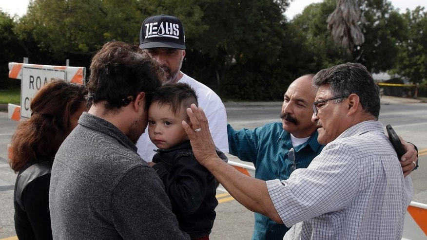 A group of local church members pray for residents who live in the neighborhood where Wednesday's police shootout with suspects took place, Thursday, Dec. 3, 2015, in San Bernardino, Calif. Multiple attackers opened fire on a banquet at a social services center for the disabled in San Bernardino on Wednesday, killing multiple people and sending police on a manhunt for suspects. (AP Photo/Chris Carlson)