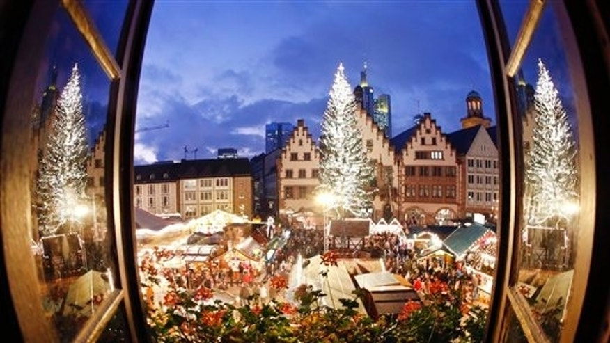 The Christmas tree of the Christmas Market is reflected in two windows in downtown Frankfurt, Germany, Friday, Dec. 4, 2015. (AP Photo/Michael Probst)