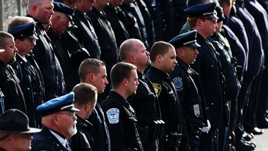 Police officers line the route of the funeral procession for St. Clair Township, Pa., officer Lloyd Reed Jr. is carried into the Cambria County War Memorial for a funeral service in Johnstown, Pa., Friday, Dec. 4, 2015.  Reed was killed responding to a domestic dispute. (AP Photo/Gene J. Puskar)