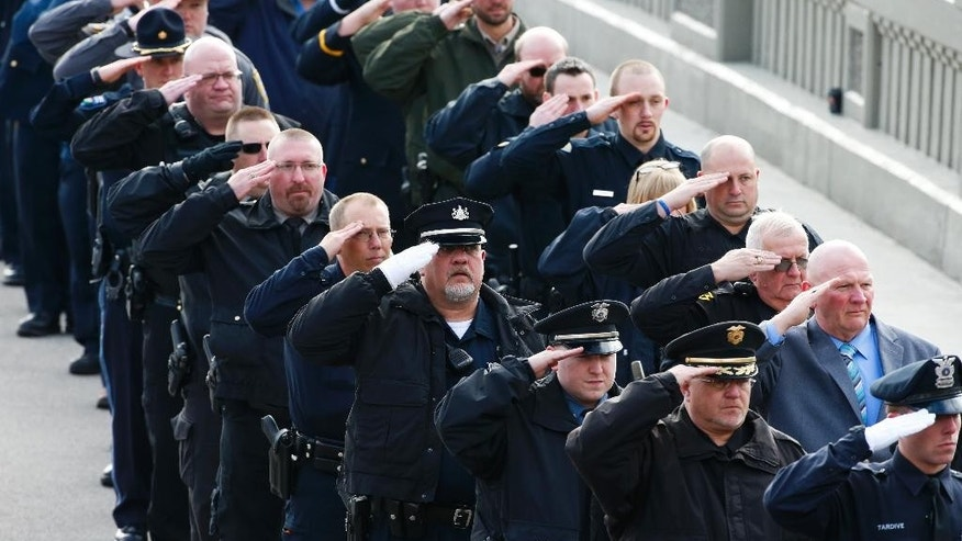 Police officers salute as the casket of St. Clair Township, Pa., officer Lloyd Reed Jr. is carried into the Cambria County War Memorial for a funeral service in Johnstown, Pa., Friday, Dec. 4, 2015. Reed was killed responding to a domestic dispute. (AP Photo/Gene J. Puskar)