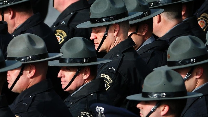 Pennsylvania State Police line the route of the funeral procession for St. Clair Township, Pa., officer Lloyd Reed Jr. is carried into the Cambria County War Memorial for a funeral service in Johnstown, Pa., Friday, Dec. 4, 2015. Reed was killed responding to a domestic dispute. (AP Photo/Gene J. Puskar)