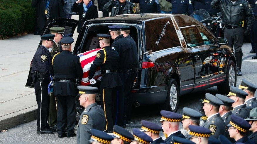 The casket of St. Clair Township, Pa., officer Lloyd Reed Jr. is carried by an honor guard of Pennsylvania State Police and Pittsburgh Police into the Cambria County War Memorial for a funeral service in Johnstown, Pa., Friday, Dec. 4, 2015. Reed was killed responding to a domestic dispute. (AP Photo/Gene J. Puskar)