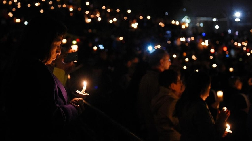 People hold candles during a vigil for shooting victims on Thursday, Dec. 3, 2015, at San Manuel Stadium in San Bernardino, Calif. A husband and wife opened fire on a holiday banquet, killing multiple people on Wednesday. Hours later, the couple died in a shootout with police. (AP Photo/Mark J. Terrill)