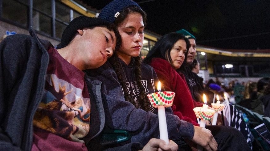 The McIntyre family from Redlands, Calif., hold candles at a vigil at San Manuel Stadium Thursday, Dec. 3, 2015, in remembrance of the 14 people lost Wednesday in the San Bernardino mass shooting. From left to right, Patrick,11, Kathleen, 13, (sister), Renee and Joe.  The parents are middle school teachers. (Tom Tingle/The Arizona Republic via AP)