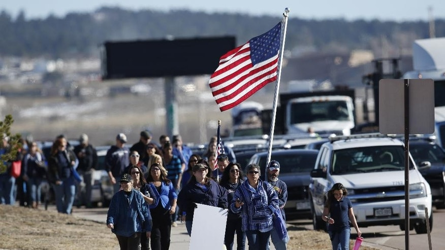 Law enforcement supporters march on sidewalk surrounding New Life Church as they wait for hearse carrying the body of slain University of Colorado-Colorado Springs police officer Garrett Swasey to arrive at a memorial service  at New Life Church Friday, Dec. 4, 2015, in north Colorado Springs, Colo. Swasey and two civilians were killed last Friday during a mass shooting incident at a Planned Parenthood clinic in the northwest part of Colorado Springs. (AP Photo/David Zalubowski)