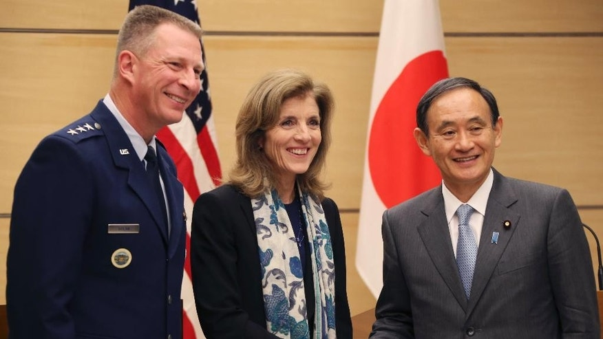 Japanese Chief Cabinet Secretary Yoshihide Suga, right, shakes hands with U.S. Ambassador to Japan Caroline Kennedy, center, as Lt. Gen. John Dolan, Commander of U.S. Forces Japan, smiles after their joint press conference at Japanese Prime Minister's official residence in Tokyo, Friday, Dec. 4, 2015. The U.S. is hastening the return of some land it holds in Okinawa, seeking to soothe local resentment over the huge American military presence on the southern Japanese island. Kennedy and Yoshihide Suga announced a plan Friday to return two sites totaling 7 hectares (17 acres) now controlled by U.S. bases to local authorities by the fiscal year that ends in March 2018. (AP Photo/Koji Sasahara, Pool)