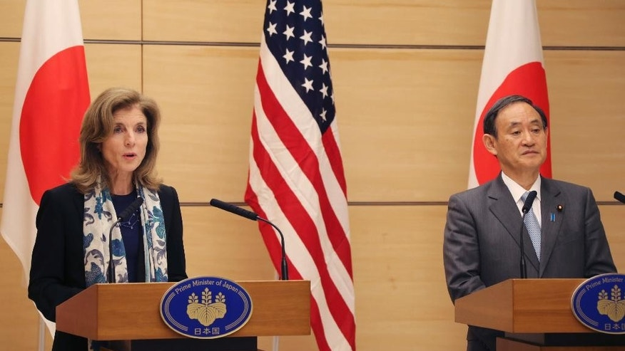 U.S. Ambassador to Japan Caroline Kennedy, left, speaks as Japan's Chief Cabinet Secretary Yoshihide Suga looks on during their joint press conference at Japanese Prime Minister's official residence in Tokyo, Friday, Dec. 4, 2015. The U.S. is hastening the return of some land it holds in Okinawa, seeking to soothe local resentment over the huge American military presence on the southern Japanese island. Kennedy and Yoshihide Suga announced a plan Friday to return two sites totaling 7 hectares (17 acres) now controlled by U.S. bases to local authorities by the fiscal year that ends in March 2018. (AP Photo/Koji Sasahara, Pool)