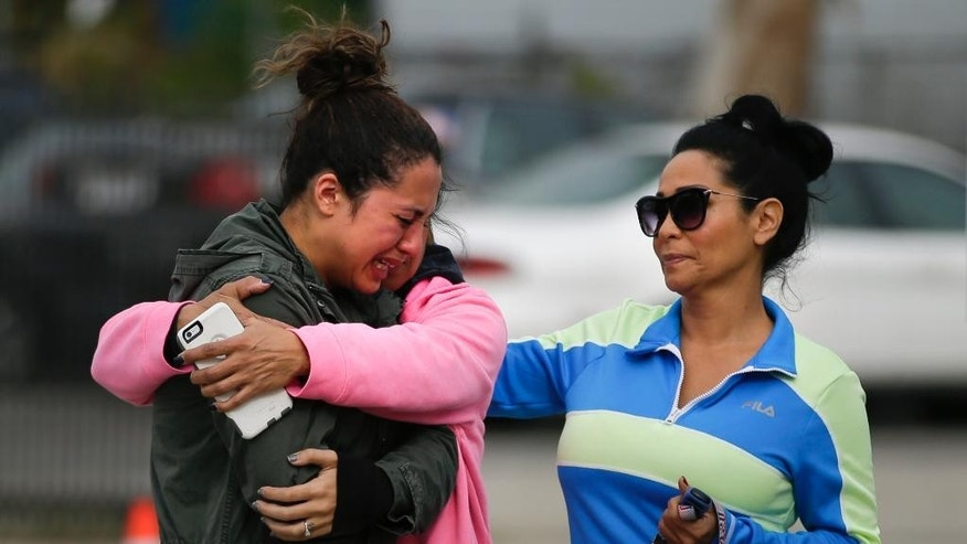 Kayla Gaskill, left, is comforted by her mother, and Connie Pegler, right, at a makeshift memorial for the victims of Wednesday's shooting rampage, Friday, Dec. 4, 2015, in San Bernardino, Calif. Gaskill said her friend Daniel Kaufman was killed in the shooting. (AP Photo/Jae C. Hong)