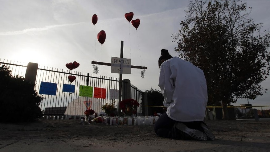 Melissa Smith prays at a makeshift memorial on Friday, Dec. 4, 2015, in San Bernardino, Calif. A husband and wife on Wednesday, dressed for battle and carrying assault rifles and handguns, opened fire on a holiday banquet for his co-workers, killing multiple people and seriously wounding others in a precision assault, authorities said. Hours later, the couple died in a shootout with police.  (AP Photo/Chris Carlson)