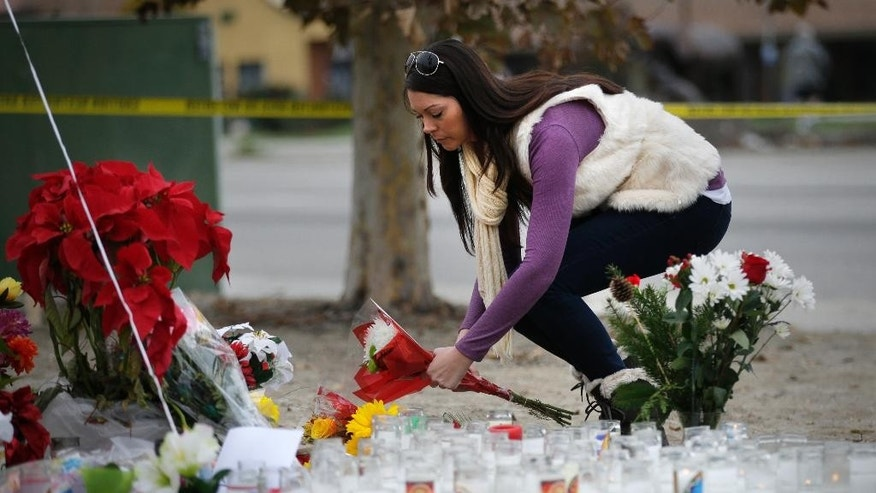 Jennifer Caballero places flowers at a makeshift memorial honoring the victims of Wednesday's shooting rampage, Friday, Dec. 4, 2015, in San Bernardino, Calif. The FBI said Friday it is officially investigating the mass shooting in California as an act of terrorism, while a U.S. law enforcement official said the woman who carried out the attack with her husband had pledged allegiance to the Islamic State group and its leader on Facebook. (AP Photo/Jae C. Hong)