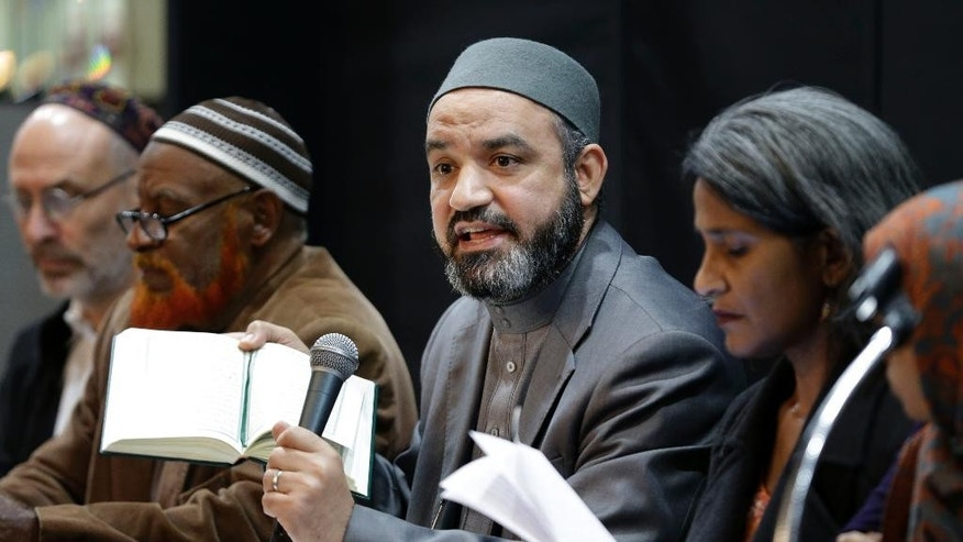 FILE - In this Wednesday, Nov. 18, 2015 file photo, Aly Kamel, an imam from the Bronx Muslim Center, holds a Quran before reading from it during a news conference in New York. Kamel joined other religious and community leaders to denounce the terror attacks in Paris. (AP Photo/Seth Wenig)