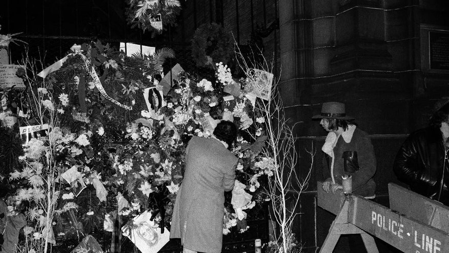FILE - In this Dec. 10, 1980 file photo, a man adjusts one of the wreaths that cover the wrought iron front gate to the Dakota apartment building where John Lennon lived. Thirty-five years ago on Dec. 8, Mark David Chapman shot and killed Lennon with a gun he purchased legally in Hawaii, a former Beatles member. (AP Photo/Lyndon Fox, File)
