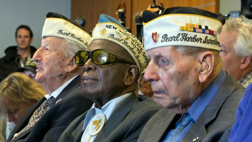 Pearl Harbor survivors Armando Galella, left, from Sleepy Hollow, NY, Clark Simmons, center, of Brooklyn NY, and Aaron Chabin, of Bayside, Queens, NY, attend a remembrance ceremony atthe Intrepid Sea, Air & Space Museum, in New York, in remembrance of the 74th anniversary of the Pearl Harbor attack, Monday, Dec. 7, 2015. (AP Photo/Richard Drew)
