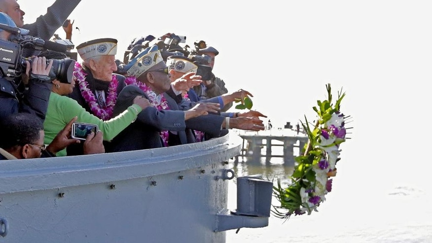 Pearl Harbor survivors Armando Galella, left, from Sleepy Hollow, NY, and Clark Simmons, of Brooklyn NY, throw a memorial wreath from the deck of the Intrepid Sea, Air & Space Museum, in New York, in remembrance on the 74th anniversary of the Pearl Harbor attacks, Monday, Dec. 7, 2015. (AP Photo/Richard Drew)