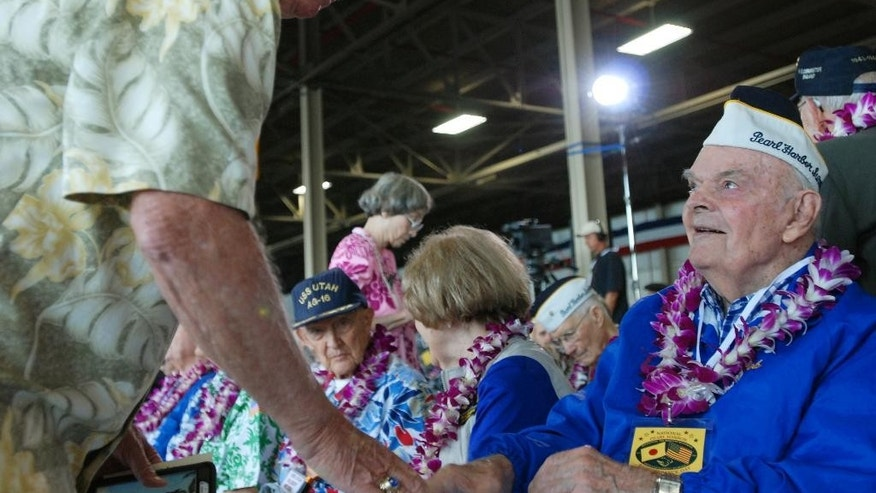 Pearl Harbor survivor Robert Irwin shakes the hand of his brother, Frank Broz, on Monday, Dec. 7, 2015, in Pearl Harbor, Hi., before a ceremony marking the 74th anniversary of the Japanese attack that launched the U.S. into World War II. (AP Photo/Audrey McAvoy)