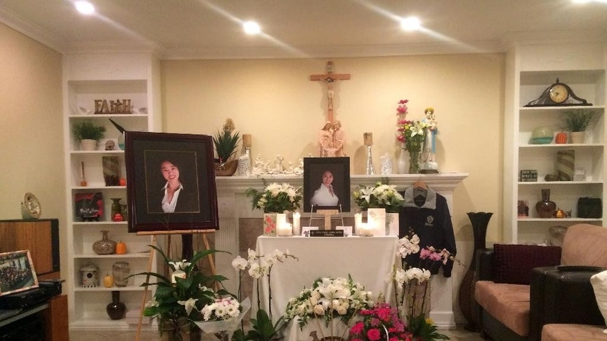 A memorial is displayed in the family home of Tin Nguyen in Anaheim, Calif., Saturday, Dec. 5, 2015. Nguyen fled Vietnam with her mother as a child in the violent aftermath of the country's long war. For her, immigrating to the U.S. meant finding a refuge from fear. She was killed last week in the shootings at a social services center in San Bernardino. (AP Photo/Christine Armario)