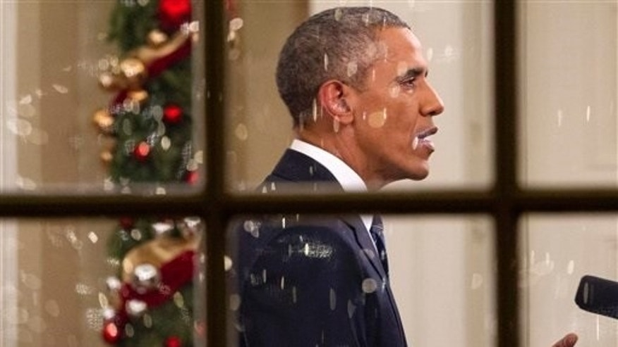 With Christmas lights reflected in the window, President Barack Obama makes an address to the nation in the Oval Office of the White House in Washington, Sunday, Dec. 6, 2015. (AP Photo/Jacquelyn Martin)