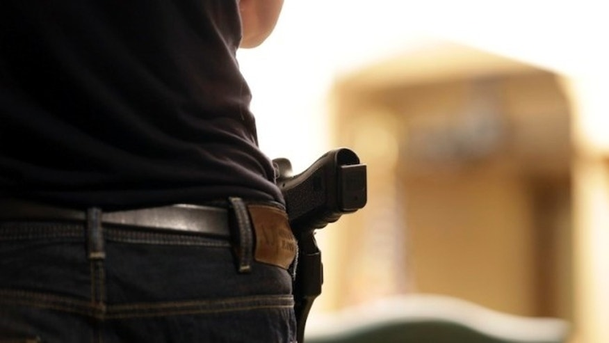 A Glock handgun is holstered on the side of Kristopher Kranz of Bloomington, Minn., as he listens during public testimony Tuesday, Aug. 20, 2013 in St. Paul, Minn. in front of a panel studying whether Minnesota's rules for carrying a gun in the Capitol need revising,  (AP Photo/Jim Mone)
