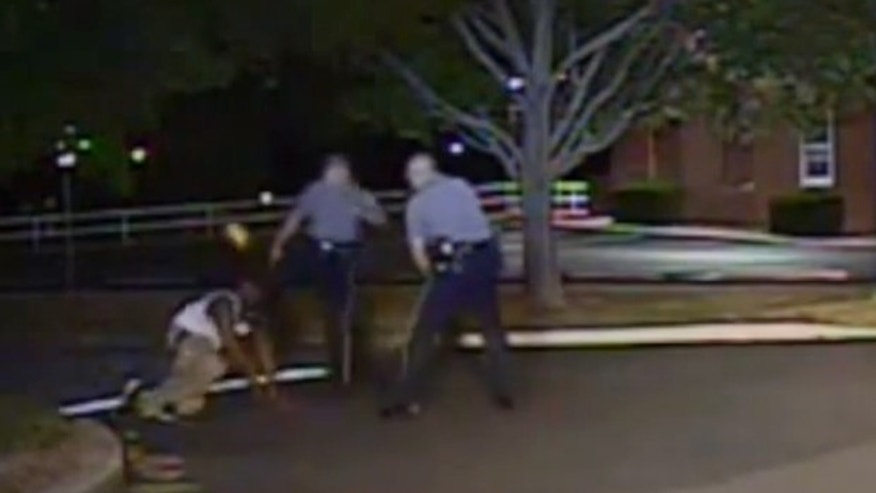 In this image from police video, Cpl. Thomas Webster, center, kicks Lateef Dickerson in the face as Dickerson is following orders to get on the ground during an arrest.