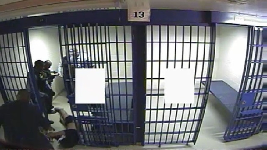 Dec. 13, 2012: This still from video released by the Chicago Police Department shows an officer dragging 38-year-old detainee Philip Coleman from his cell after a struggle with officers during which he was hit with a stun gun. The white boxes are to give detainees privacy while using the cell toilets. (Chicago Police Department)