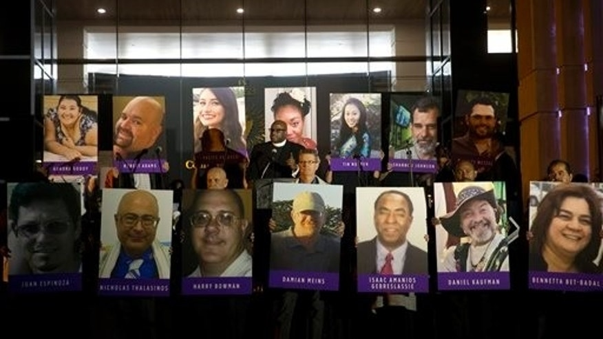 """San Bernardino County employees hold up photos of the San Bernardino shooting victims during a candlelight vigil on Monday, Dec. 7, 2015, in San Bernardino, Calif. The husband and wife who opened fire on a social services center last week had been radicalized """"for quite some time"""" and had taken target practice at area gun ranges, in one instance just days before the attack that left 14 people dead, the FBI said Monday. (AP Photo/Jae C. Hong)"""