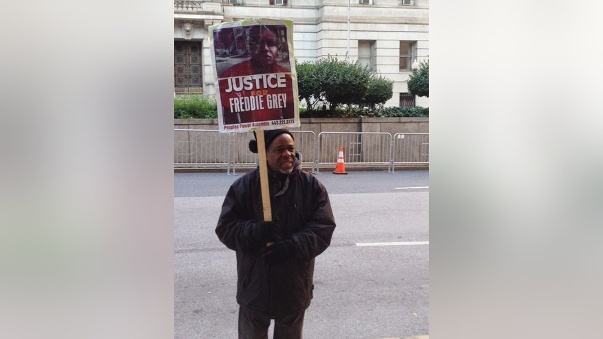 Demonstrator Arthur Johnson carries a sign advocating justice for Freddie Gray on Monday, Dec.  7, 2015, outside the courthouse in Baltimore where the trial of Offcer William Porter enters its second week. (AP Photo/David Dishneau)