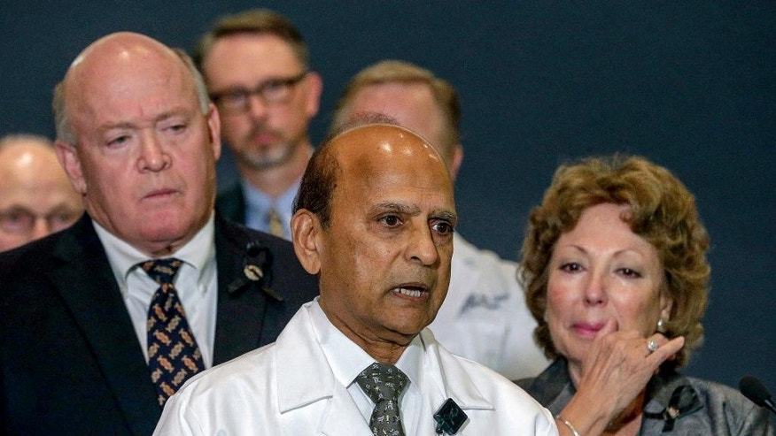"Dr. Dev GnanaDev, chief of surgery at Arrowhead Regional Medical Center, center, comments on the victims of the San Bernardino shootings at a news conference in San San Bernardino, Calif., on Monday, Dec. 7, 2015. ""What really bothers me most is that none of the 14 who perished had a chance,"" he said. Josie Gonzales, San Bernardino County fifth district supervisor, is seen right. (AP Photo/Nick Ut)"