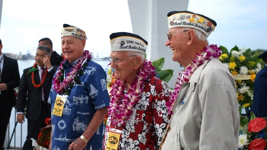 Pearl Harbor survivors Lou Cantor, left, John Hughes, center, and Ed Schuler, right, pose for photos at the USS Arizona Memorial in Pearl Harbor, Hawaii, Monday, Dec. 7, 2015. The three gathered on the memorial for a wreath-laying ceremony on the 74th anniversary of the Japanese attack on Pearl Harbor. (AP Photo/Audrey McAvoy)