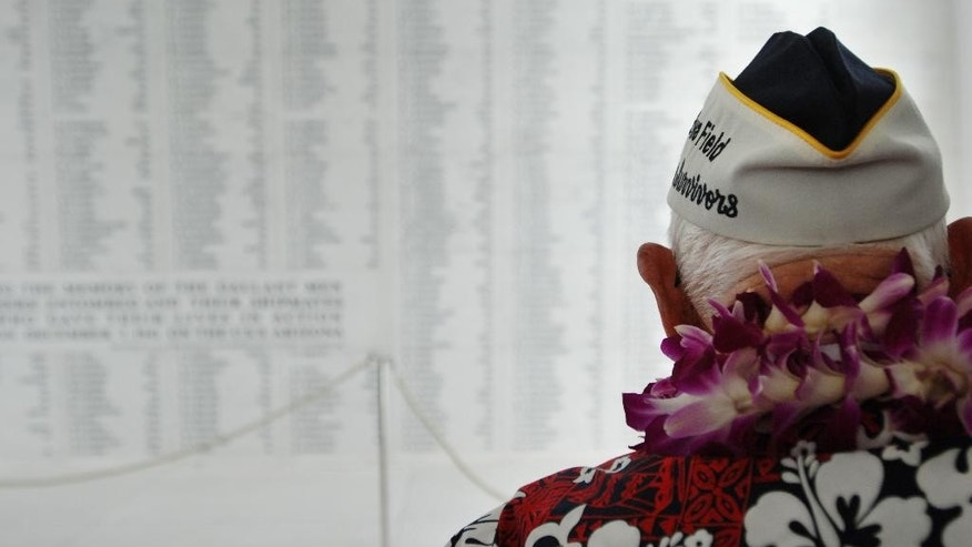 Pearl Harbor survivor John Hughes pauses to look at a wall engraved with the names of USS Arizona sailors and Marines killed in the attack on Pearl Harbor after a wreath-laying ceremony at the USS Arizona Memorial in Pearl Harbor, Hawaii, Monday, Dec. 7, 2015. A memorial and a wreath-laying ceremony were marking the 74th anniversary of the Japanese attack. (AP Photo/Audrey McAvoy)